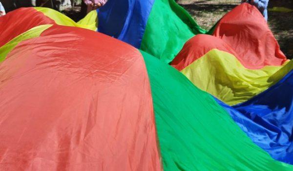 bambini giocano con un paracadute in giardino